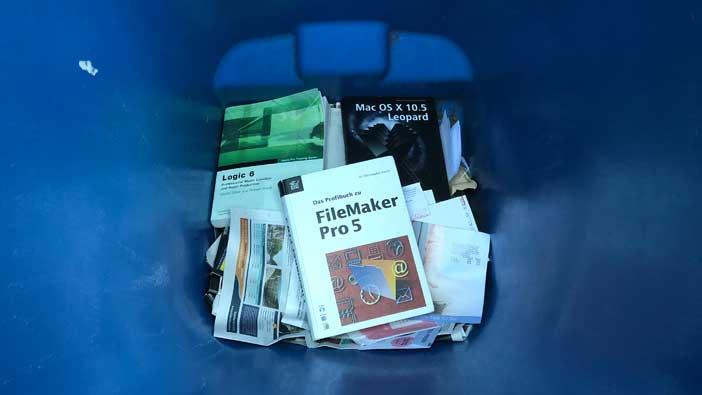 Drei Computerbücher in der blauen Tonne